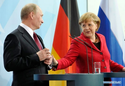 Russian President Vladimir Putin with German Chancellor Angela Merkel attend a press conference in Berlin in June